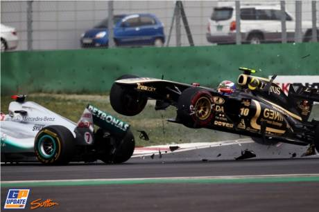 Vitaly Petrov (Lotus Renault GP, R31) launches himself over Michael Schumacher (Mercedes GP F1 Team, MGP W02)